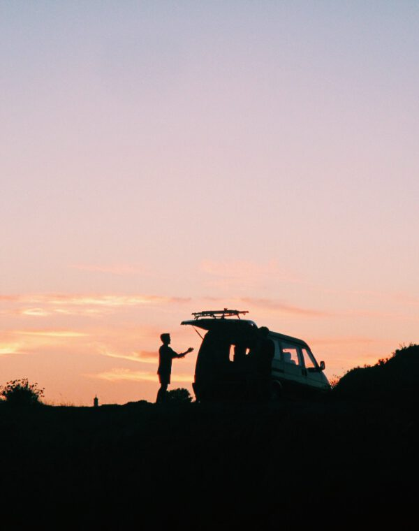 Young man putting surfboard in a van at sunset by the beach